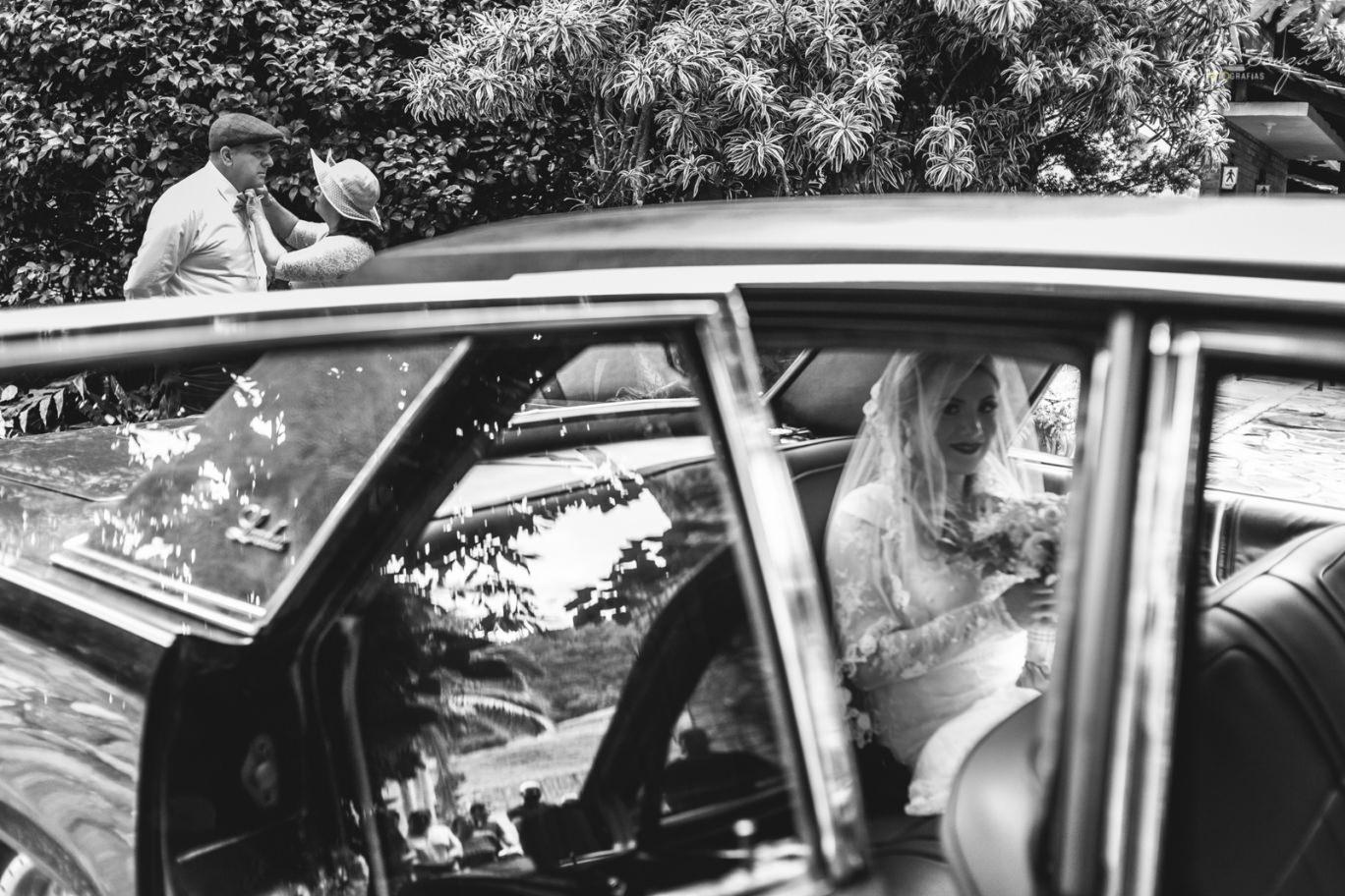 noiva no carro e um momento dos pais da noiva ao fundo
